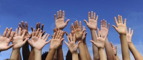 Multiethnic raised hands and writing volunteer